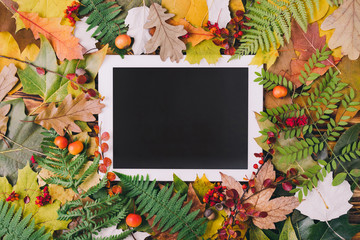 Autumn composition with tablet and colorful leaves on wooden background. Top view, flat lay, copy space.