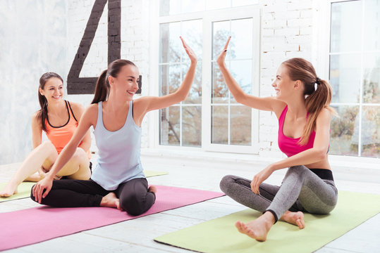 Three young girls giving high five in fitness studio