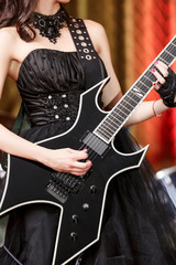 close-up of a woman on stage playing on electro guitar. The girl rockstar in a black dress