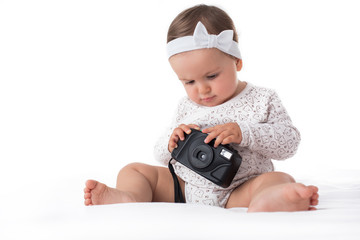 Beautiful baby girl playing with camera on white background