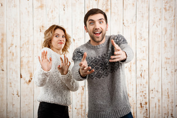 Man stretching to camera smiling girl refuse over wooden background.