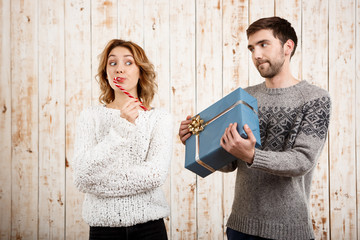 Couple smiling holding christmas candy and gift over wooden background.