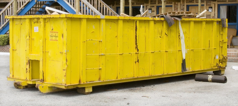 Huge yellow industrial dumpster full of construction and renovation debris in motel parking lot. Motel stairs in background. Horizontal.