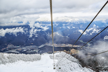 Cableway lift with ski slopes on cloudy sky and snowy mountain background beautiful winter scenic landscape
