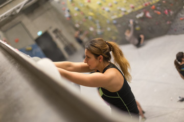 sporty woman in boulder climbing hall