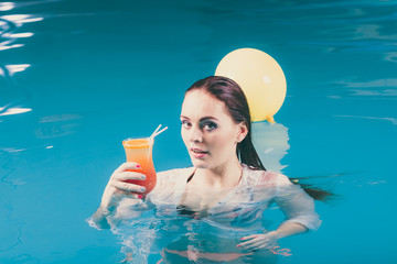 Happy woman with balloons and cocktail in water.