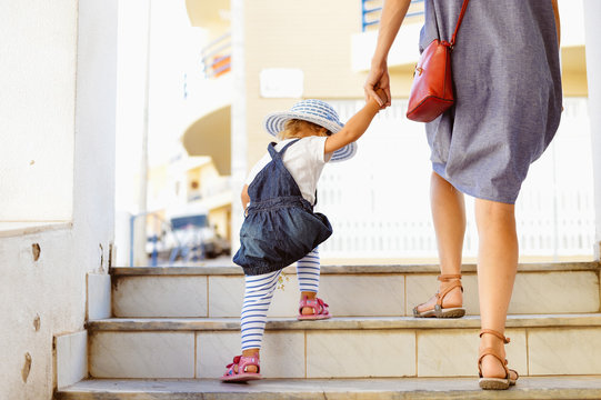 Back view of beautiful toddler girl walk with mother, stairs outdoors background, closeup view