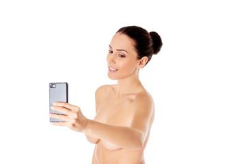 Nude beautiful woman taking selfie on white background.