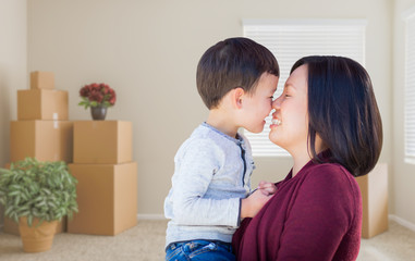 Young Mixed Race Chinese Mother and Child in Empty Room with Packed Moving Boxes and Plants.