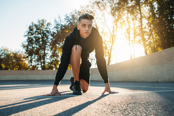 Young sportsman preparing for run, sunset light. Sprinter training before sport competitions. Evening workout. Competition, sport ,beginning, commitment, speed concept