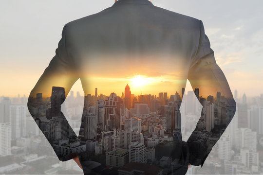 A back turned businessman cityscape and sunset as vision of leader concept.