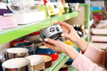 Hands of young woman selecting bowl in pet shop, close up view
