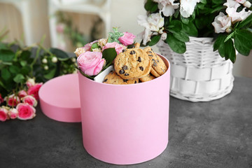 Box with beautiful flowers and cookies on dark textured table
