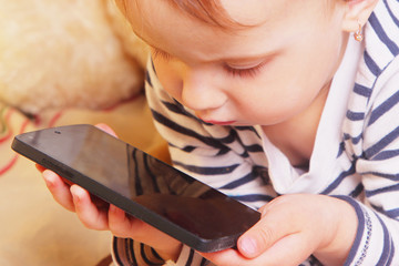 Social Media addiction. beautiful baby girl  holding phone (psyc