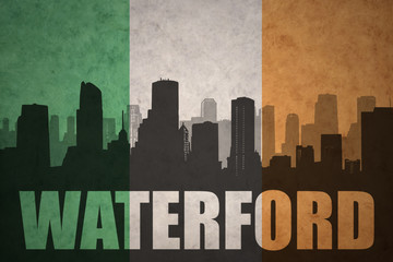 abstract silhouette of the city with text Waterford at the vintage irish flag