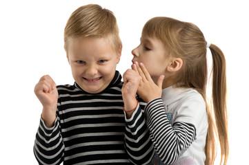 Girl whispering a secret in the ear of the boy.