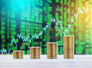 Stacks coins with financial stock charts as background.