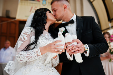 Exuberant kissed wedding couple with two pigeons at hand.