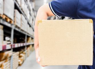 Delivery man in blue uniform holding the box on warehouse blurre