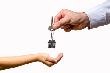 in the hand of the adult gives the house key to the child's hand on white background