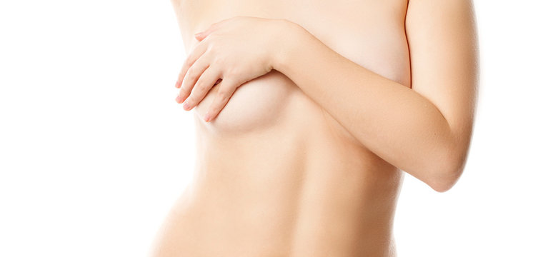 Cropped photo of a young woman's breast. She is covering her breast.