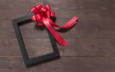 Frame picture and red ribbon are on the wooden background with e