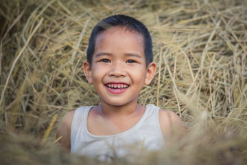 Happy Children wearing a white shirt on straw with a bright smile.