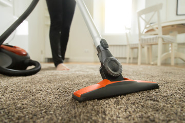 Close up of the vacuum cleaner, focus on the brush, woman cleaning the carpet. Home, housekeeping concept