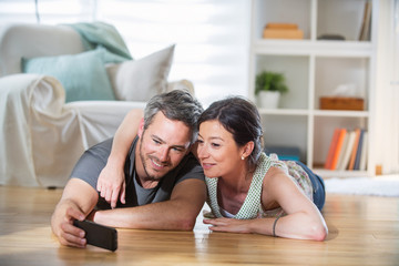 At home, couple lying on wooden floor take a selfie with a phone