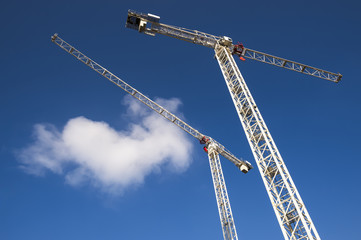 Modern hi-rise construction site with cranes towering into bright blue sky with puffy white clouds