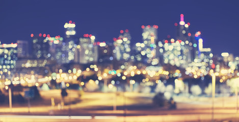 Vintage toned blurred Denver city lights at night, urban abstract background.