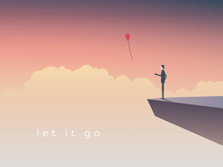 Businessman standing on a cliff letting go  balloon.