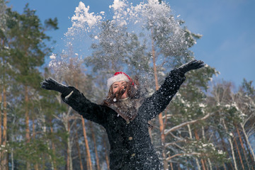 Young beautiful smiling woman throwing snow in the air in winter holidays