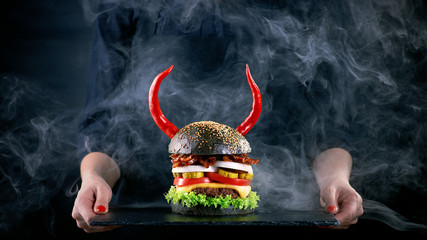 Wall Mural - Devil burger with bacon and vegetables on black slat plate in wo