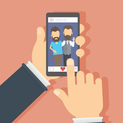Men on the screen. Hand holding smartphone with photo of the male frends. Concept of applications or social networks. Like button.