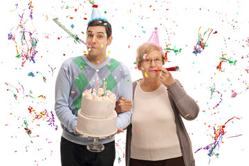 Young man with birthday cake and mature woman blowing party horns