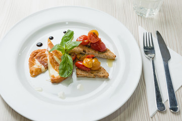 Delicious toast sandwiches with fried cheese, tomatoes, olive oil and basil