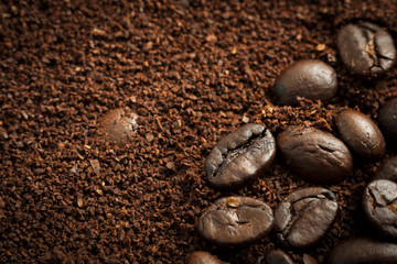 Closeup of mixed heap of roasted coffee beans and ground coffee with copy space
