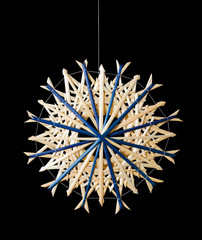 Blue straw star Christmas decoration on black background. Handmade decor for windows, as gifts or to hang on the xmas tree, traditionally made from natural straw. Macro photo front view close up.