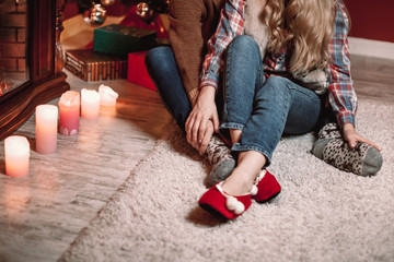 A couple of lovers resting by the fireplace in the Christmas room. Feet in woolen socks warming in winter time.