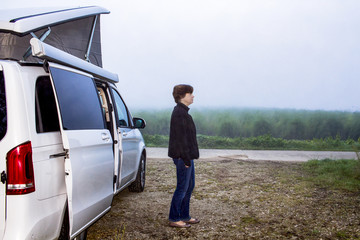 Woman is standing in front of the camping bus