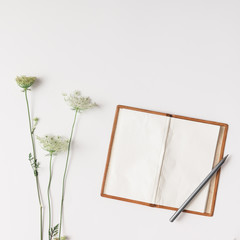 White flowers and vintage notebook arranged on bright background