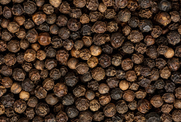 Black pepper grains as background close up
