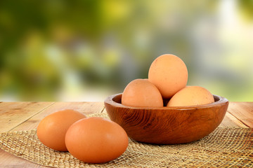 Eggs on wooden table and blur nature background.