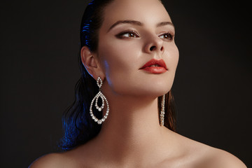 Beautiful woman in luxury fashion earrings. Diamond shiny jewelry with brilliants. Sexy retro style portrait. Model with glamour accessories jewelery, fashion makeup, clean shiny skin and wet hair
