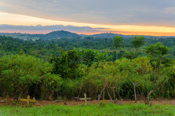 Simple wooden crosses and graves in front of lush jungle and dramatic sunset in Congo