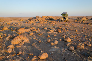 Camping with a 4x4 and roof top tent in a rocky part of Angola's Namib Desert.
