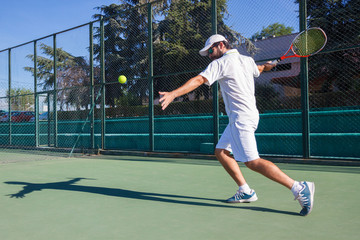 Professional tennis player playing a game of tennis on a court. He is about to hit the ball with the racket. The ball is suspended in the air.
