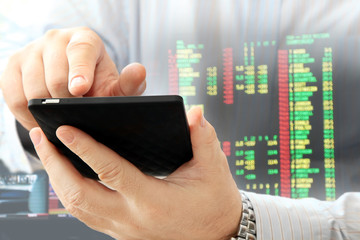 Close up of man using smartphone on stock market background