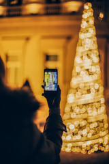 Woman taking a picture of Christmas tree at the street